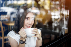 Asia girl drinking white cup of coffee in cafe royalty free stock photos