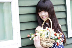 Asia girl with flowers. Charming Asia girl holding a basket of flowers smiling outdoor Royalty Free Stock Photo