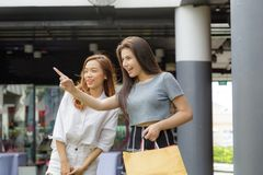 Girl shopping in department store. Asia girl and friend ethnic German-Thai go shopping holding bag and smart phone in a department store Stock Photos