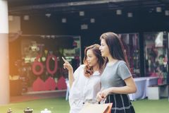 Girl shopping in department store. Asia girl and friend ethnic German-Thai go shopping holding bag and smart phone in a department store. Soft flare filter Royalty Free Stock Images