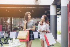 Girl shopping in department store. Asia girl and friend ethnic German-Thai go shopping holding bag and smart phone in a department store. Soft flare filter Stock Images