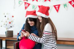 Asia girl friends wear santa hat in merry christmas party using Stock Photo