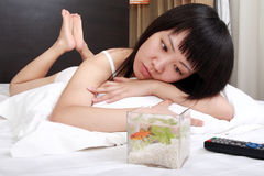 Asia girl with her goldfish. A beautiful Asian girl is seeing the expression of the goldfish on the bed Stock Photography