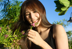 Asia girl look into pink flower and smile Stock Photo