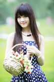 Asia girl next door. Holding a basket of flowers outdoor in summer Stock Photography