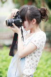 Asia girl shooting. Asia girl holding a camera shooting outdoor Stock Photo