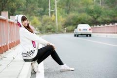 Asia girl sitting roadside stock images
