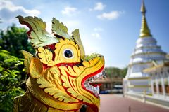 Asia gold red lion statue with temple background. Asia gold red lion statue with blurry temple background stock image