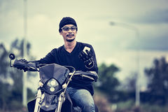 Asia handsome man biker holding telephone on the motorcycle Stock Photography
