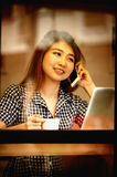 Asia happy woman talking  phone in cafe and enjoying coffee Royalty Free Stock Images