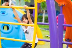Asia kid girl having fun to play on children`s climbing toy at school playground,back to school outdoor activity.  stock photo