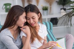 Asia lesbian lgbt couple sitting on sofa reading book and hug to royalty free stock images
