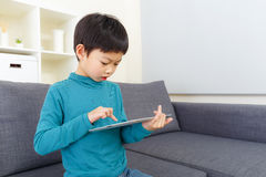 Asia little boy concentrate on using tablet. At home Royalty Free Stock Photo