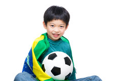 Asia little boy draped Brazil flag and holding soccer ball. Isolated on white royalty free stock photos