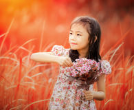 Asia little girl laughing in a meadow Stock Photos