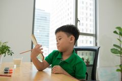 Asia little student boy studying and doing his homework at home, on the table, home education, thinking action royalty free stock image