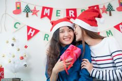 Asia lover Girlfriend kiss cheek and give Christmas gift at xmas. Party,Asia girl friends wear santa hat exchange red gift box with smiling face,gift giving Stock Images