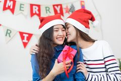 Asia lover Girlfriend kiss cheek and give Christmas gift at xmas. Party,Asia girl friends wear santa hat exchange red gift box with smiling face,gift giving Stock Photos