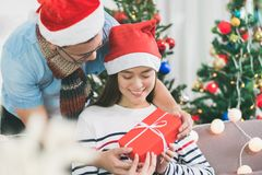 Asia lovers couple, boyfriend surprise girlfriendby giving Chris. Tmas present at sofa with xmas decoration tree at house party,Holiday celebrating season Royalty Free Stock Images