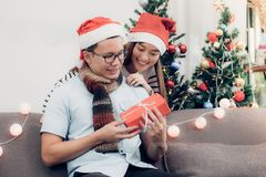 Asia lovers couple,girlfriend surprise boyfriend by giving Chris. Tmas present at sofa with xmas decoration tree at house party,Holiday celebrating season Stock Photography