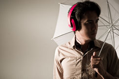 Asia man. With headphone on his head using umbrella Royalty Free Stock Images