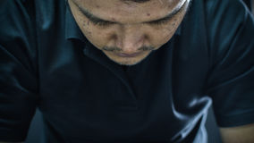 Asia man depression or sadness in dark style. Asia man in black polo shirt have a depression gesture with stress and sadness concept on black background dark Stock Images