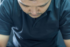 Asia man depression or sadness in dark style. Asia man in black polo shirt have a depression gesture with stress and sadness concept on black background dark Royalty Free Stock Photos