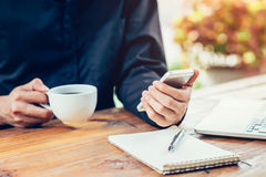 Asia man hand using phone on wood table in coffee shop with vint Royalty Free Stock Photos