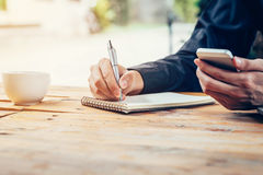 Asia man hand writing notebook paper and using phone on wood tab Royalty Free Stock Image