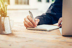 Asia man hand writing notebook paper on wood table in coffee sho Royalty Free Stock Image