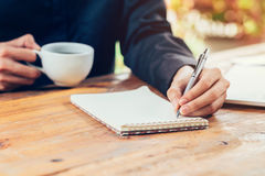 Asia man hand writing notebook paper on wood table in coffee sho Stock Photo