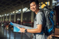 Asia man holding map with bag backpack alone in the train station, preparing,planing and find location for travel trip. Asia man holding map with bag backpack stock photo