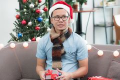 Free Asia Man Holding Small Gift Box And Looking At Friend Feel Envious Of Other Bigger Present And Sit Alone On Sofa,jealous And Lone Royalty Free Stock Photo - 105686525