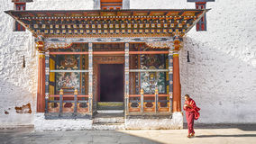 The asia man monk walks near the main door tower prayer at Paro Dzong,. PARO BHUTAN MARCH 02 2016 : the asia man monk walks near the main door tower prayer at Royalty Free Stock Photography