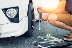 Asia man with a white car that broke down. On the road.Changing tire on broken car on road Royalty Free Stock Photography