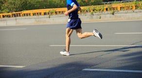 Marathon runner running on city road. Asia marathon young fitness men runner is running on city road Stock Photos