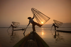 ASIA MYANMAR INLE LAKE. Fishermen at sunrise in the Landscape on the Inle Lake in the Shan State in the east of Myanmar in Southeastasia Royalty Free Stock Photo