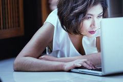 Asia office woman lying on floor with laptop at home Royalty Free Stock Photography