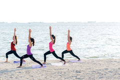 Asia people group making warrior pose on beach, fitness, sport, yoga and healthy lifestyle Stock Images