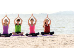 Asia people group making warrior pose on beach, fitness, sport, yoga and healthy lifestyle. Royalty Free Stock Images