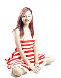 Asia pretty girl in red white dress sit on floor. In studio white background Royalty Free Stock Photos