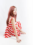 Asia pretty girl in red white dress sit on floor. In studio white background Stock Photos