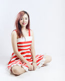 Asia pretty girl in red white dress sit on floor. In studio white background Stock Photography