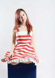 Asia pretty girl in red white dress sit on floor. In studio white background Royalty Free Stock Image