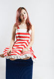 Asia pretty girl in red white dress sit on floor. In studio white background Royalty Free Stock Photography