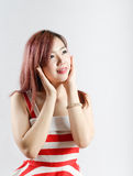 Asia pretty girl in red white dress sit on floor. In studio white background Royalty Free Stock Images