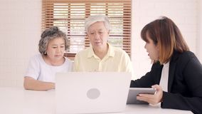 Asia smart female agent offers health insurance for elderly couples by document, tablet and laptop. Aged Asian couple consulting. Asia smart female agent offers stock footage