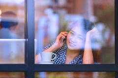 Asia smile woman talking  phone in cafe and enjoying coffee Stock Images