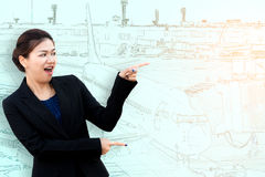 Asia surprised businesswoman pointing to side with aeroplane. In airport Royalty Free Stock Images