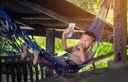 Asia tailandesa, muchacho sonriente que toma selfies divertidos con su phon móvil Imagen de archivo